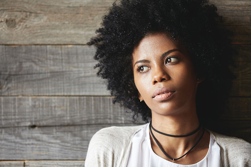 African-American woman looking off to side in contemplation.